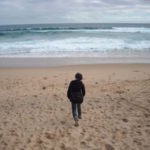 一人で浜辺を歩いている少年