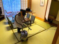 和室に掃除機をかけている客室清掃スタッフ