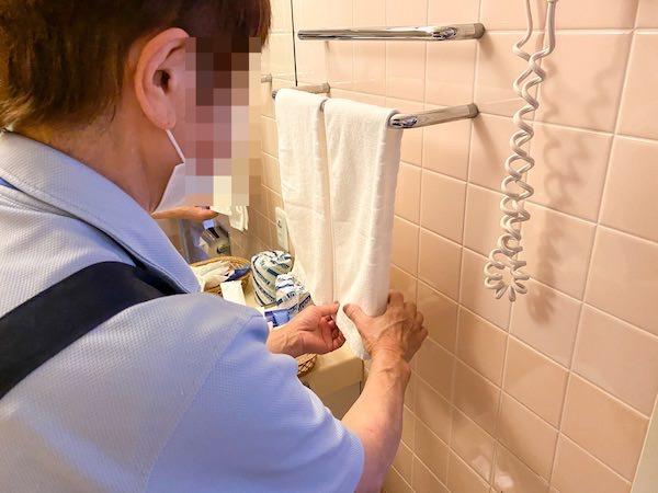 ハンドタオルを補充している清掃スタッフ