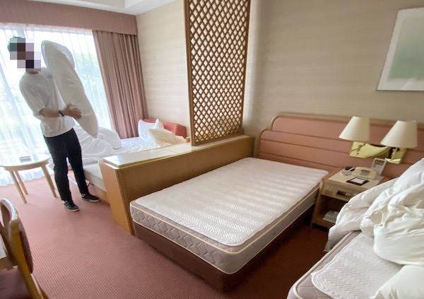 ベッドメイキング中のリゾートバイト客室清掃スタッフ