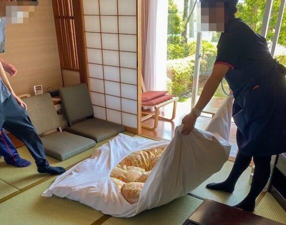 和室をベッドメイキング中の客室清掃スタッフ