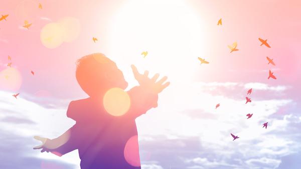 空に向かって両手を広げている男性