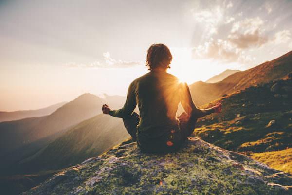 頂上に座って朝日を見ている男性