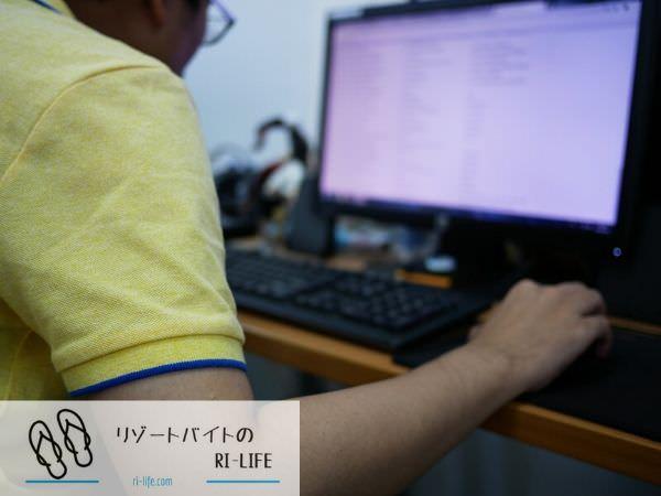 パソコンで宿泊者の予約管理をしているリゾートバイトスタッフ