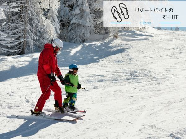 小さな子供にスキーの滑り方を教えているインストラクター