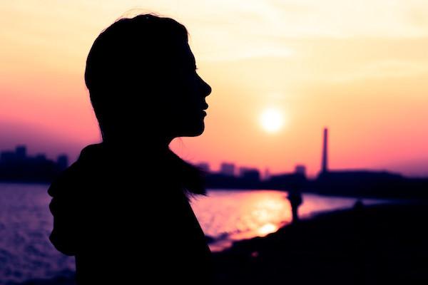 沈む夕日と女性のシルエット