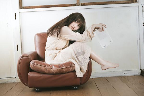 一人がけソファーで本を読んでいる女性